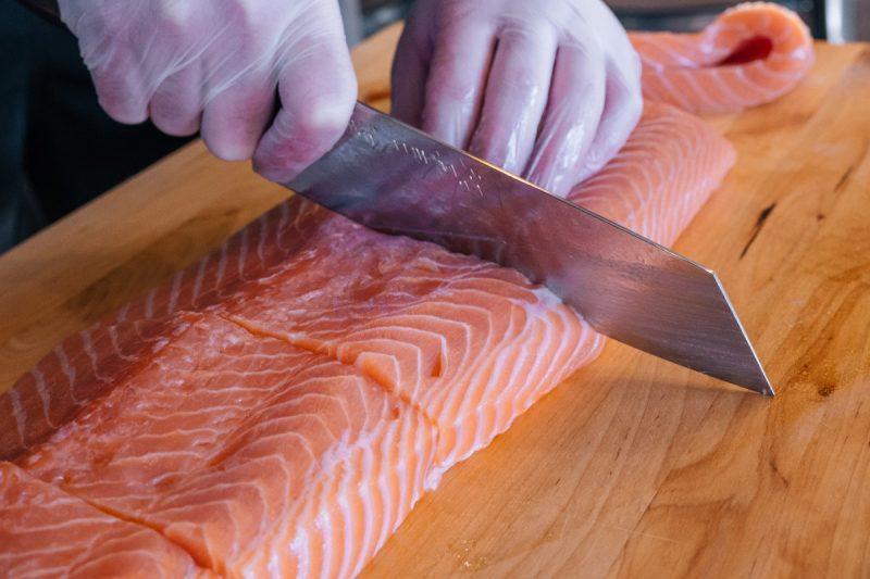 Chef Cutting Fresh Salmon for Poke Bowl